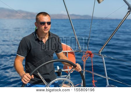 Man skipper steers sailing boat on the Sea. Luxury yacht.