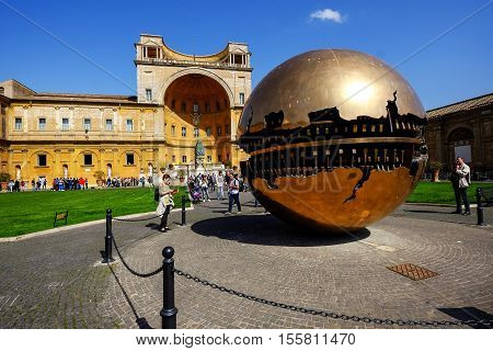VATICAN CITY - MARCH 24, 2015: Tourist visiting a famous sculpture, The Sphere Within Sphere,  inside the Vatican museum on a beautiful sunny day. The sculpture created by Italian sculptor Arnaldo Pomodoro,