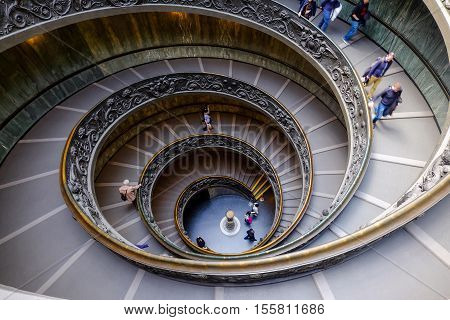 VATICAN CITY - MARCH 24, 2015: Tourist visiting the Vatican Museum and walking down the famous stairs,  the Vatican spiral staircase, on March 24, 2015. The Spiral staircase was designed by Giuseppe Momo in 1932 and located in the Vatican Museums in Vatic