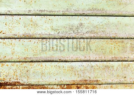 photographed close-up of a metal surface painted in green color, on which there was rust