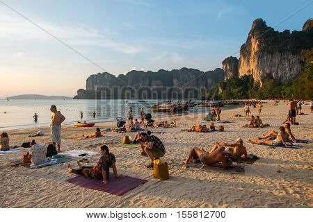 KRABI - JANUARY 20, 2015 : Tourist relaxing and sunbathing on a nice day JANUARY 20, 2015 at Railay Beach in Krabi, Thailand. Railay Beach is a small peninsula with white sand beaches, soaring limestone cliffs, viewpoints, caves and a lagoon
