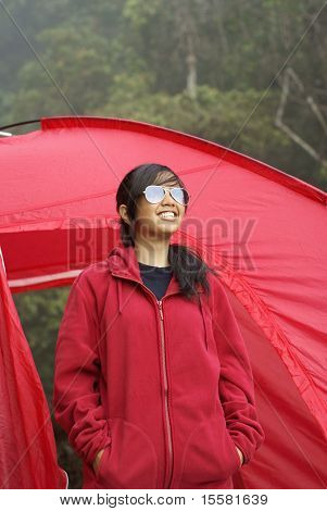 Happy asian girl outside red tent