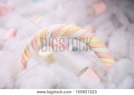 Rainbow shape of pastel colored marshmallow on a cotton background. Minimalism style.
