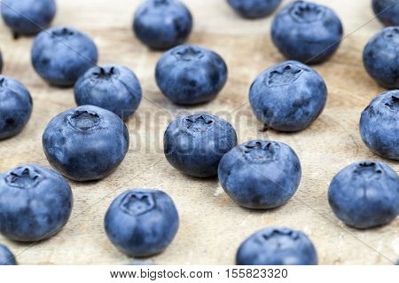 photographed closeup harvest ripe blueberries, berries spread out on an old wooden board, from top's photos