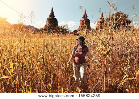 Rear view of woman traveler with a backpack walking through the field to the ancient Buddhist stupas. Birma. Concept of travel and adventure in Asia.