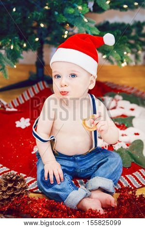 Lifestyle portrait of happy funny white Caucasian baby boy in jeans and New Year Christmas Santa hat sitting on floor eating cookie indoor at home loking in camera