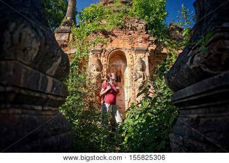 Woman traveling with backpack and looks at ancient Buddhist stupa of the temple complex In Dein Inle Lake. Mayanmar Traveling along Birma freedom and active lifestyle concept