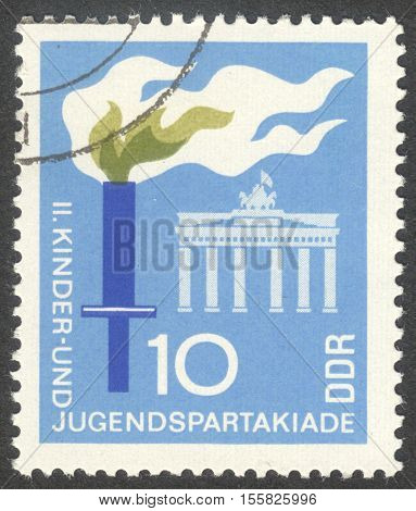 MOSCOW RUSSIA - CIRCA OCTOBER 2016: a post stamp printed in DDR shows the Brandenburg Gate and a torch the series
