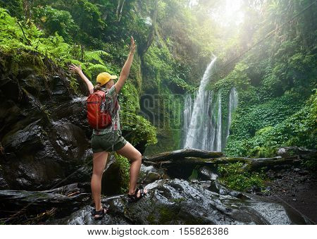 young woman backpacker looking at the waterfall in wild jungles. Ecotourism travel concept and discovery of beautiful places. Indonesia.