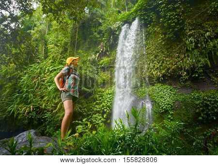 happy young woman backpacker looking at the waterfall in jungles. Ecotourism concept image travel girl