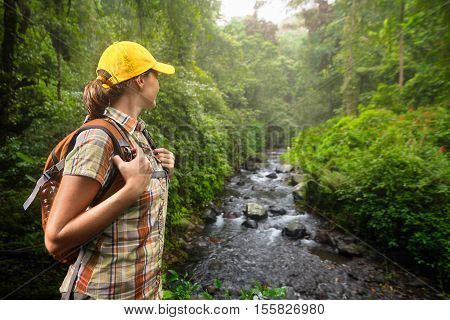 Young woman hiker with backpack standing and enjoying rain forest and river view. Lombok Indonesia. Tourist hiking in the deep jungle