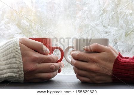 two people hold red and white cup across from a window with frost / spend time together warming favorite drink