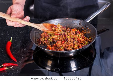 Chef preparing dishes in a frying pan. Cooking.