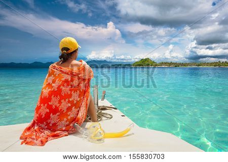 Woman traveler sit at the stern of boat at sunny day looking to sea among the islands Gili Nango. Indonesia