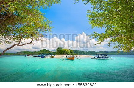 Beautiful tropical uninhabited island on background of green mountains.