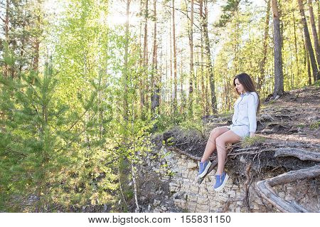 Young woman hiker sits on the edge of the cliff and enjoying forest in the mountains