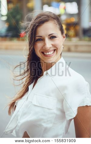 Closeup portrait of young smiling Caucasian woman girl with blue eyes with messy blond long hair on windy day outdoor toned with Instagram filters old vintage retro film effect style