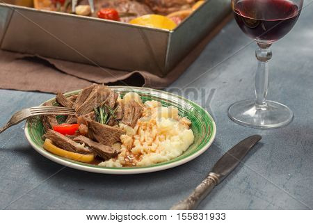 Slices of braised beef with mashed potatoes on stone surface with glass of red wine
