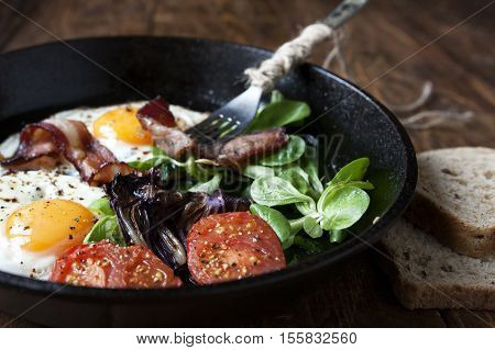 Breakfast set. Pan of fried eggs with bacon, fresh tomato, sage and bread on dark serving board over black wooden background, top view, copy space