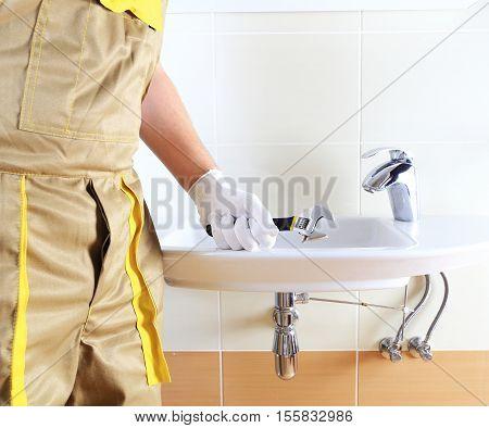 Plumber In Uniform In Bathroom