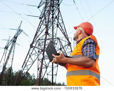 Electrical Engineer Working. Talking On The Phone And Working Working On A Laptop