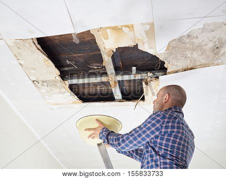 Man Collecting Water In Basin From Ceiling