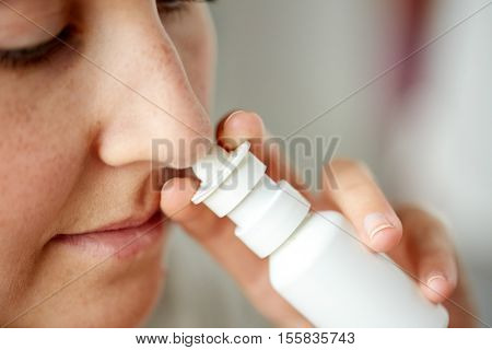 healthcare, flu, rhinitis, medicine and people concept - close up of sick woman using nasal spray