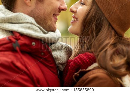 love, relationships, season and people concept - close up of happy young couple kissing outdoors