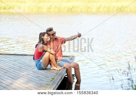 holidays, vacation, love and people concept - happy teenage couple taking selfie on smartphone and sitting on river berth at summer