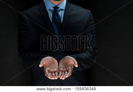 business, bankruptcy, people and crisis concept - close up of businessman in suit with empty hands over black