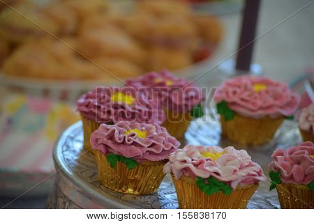 A silver tray of cupcakes decorated like flowers with tray of sandwiches in the background.