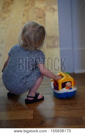 A white female toddler in a grey dress plays with toys.