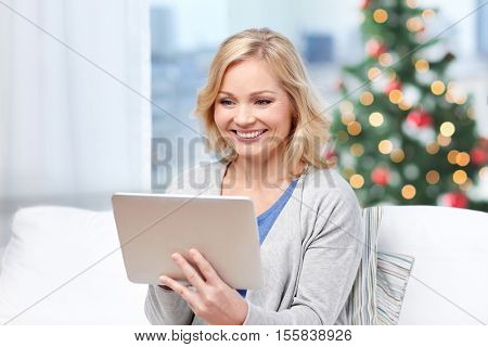 people, technology, holidays and internet concept - happy middle aged woman with tablet pc computer at home over christmas tree lights background