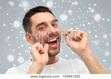 dental hygiene, care, people and winter concept - smiling young man with floss cleaning teeth over snow on gray background