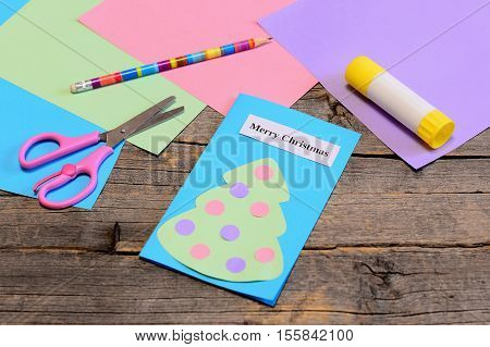 Christmas card tutorial. Paper greeting card with text Merry Christmas, pencil, glue stick, colored paper sheets, scissors on old wooden table. Fun children winter activity at home or in kindergarten