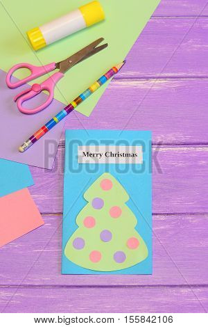 Paper card Merry Christmas. Cute greeting card with paper Christmas tree, scissors, glue stick, pencil, colored paper set on lilac wooden background. Simple children Christmas paper crafts