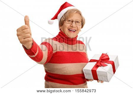 Cheerful senior holding a christmas present and giving a thumb up isolated on white background