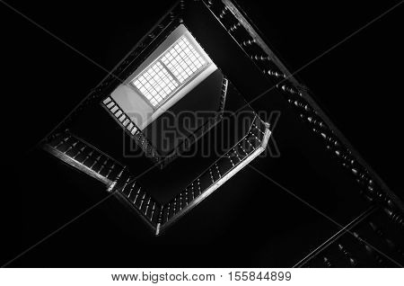 Outlines of the square staircase in building in low light with attic window. Bottom view