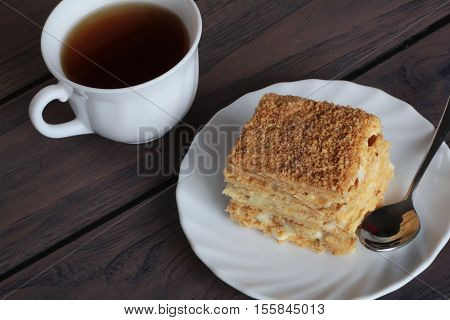 Napoleon cake and a cup pf tea on dark wooden background