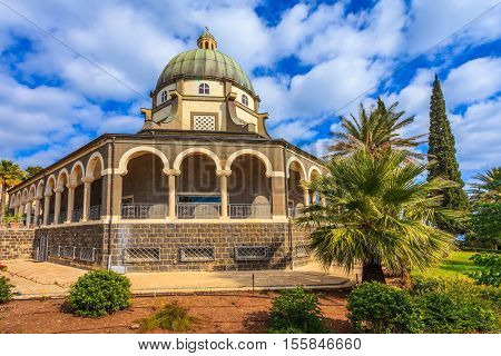 Israel, the shores of Lake Kinneret. Catholic monastery and a small church Mount Beatitudes. Dome and colonnade surrounded by cypress and palm trees.