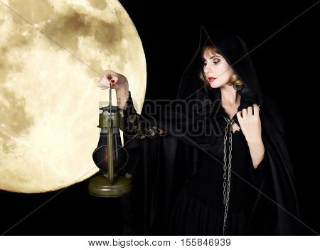mysterious young woman holding rope and old flashlight. on a dark moon background.