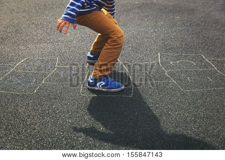 little boy playing hopscotch on playground outdoors