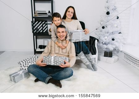 Family exchanging Christmas gifts near a Christmas tree