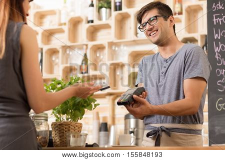 Smiling Barista With Costumer Paying By Card