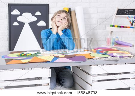 Thoughtfull Boy Is Sitting At Desk