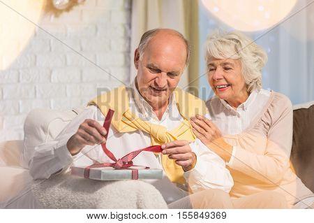 Senior Man Unwrapping Christmas Gift
