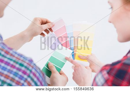 Close shot of man's and woman's hands taking color pickers
