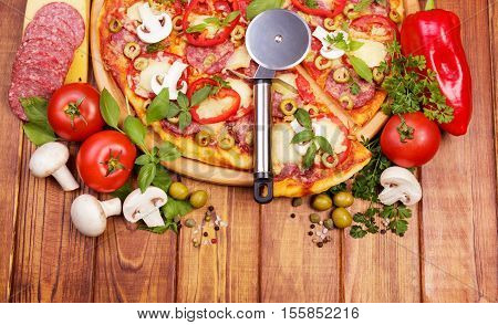 Pizza with salami, mushrooms and vegetables, knife wheel on a background of dark wood.
