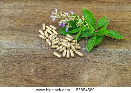 Close up fresh flower Vitex trifolia Linn or Indian Privet with green leaf is herb in Thailand and drug pill on wooden background