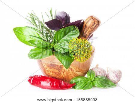 Fresh garden herbs in mortar. Basil, rosemary, dill, chili pepper, garlic. Isolated on white background